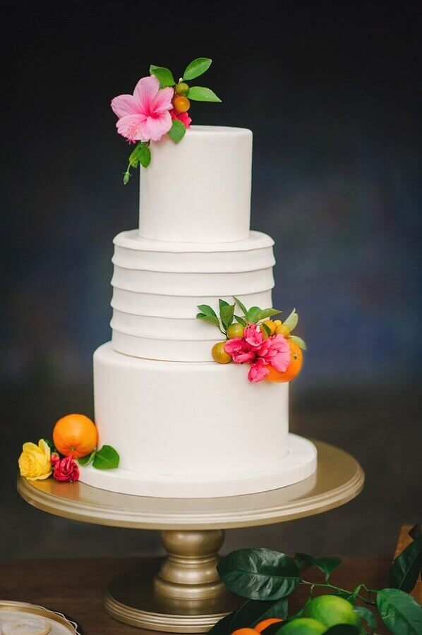 tropical party theme wedding cake decorated with colorful flowers Photo Brides