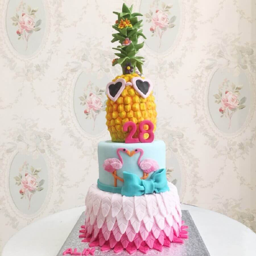 tropical cake with flamingos and pineapple on top Photo Debogato