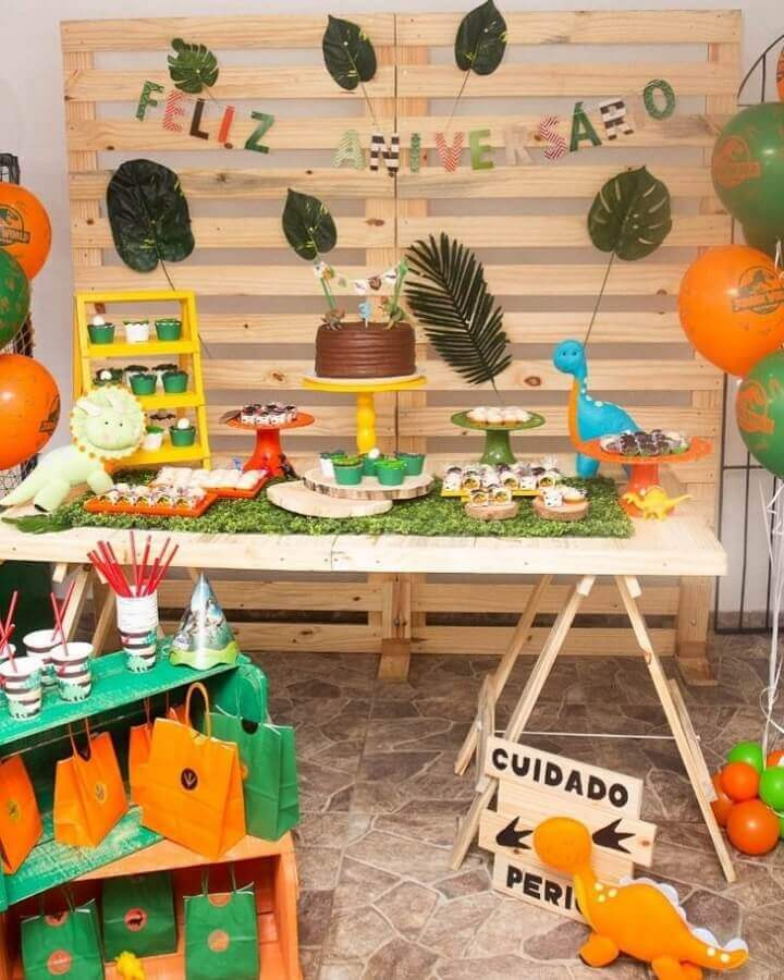 pallet panel decorated with large leaves for dinosaur party
