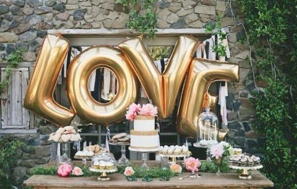 Metallic balloons on the cake table transform the engagement decor
