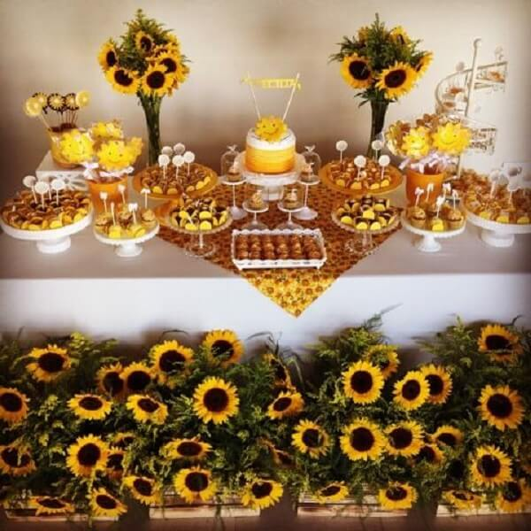 Wooden boxes and flowers decorate the table of the sunflower theme party cake