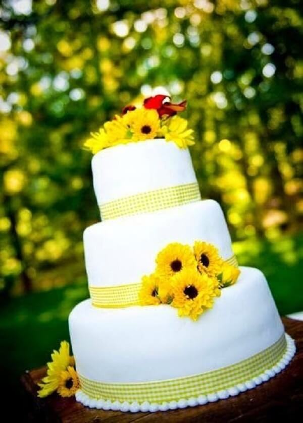 Three-story cake with sunflower party theme flowers