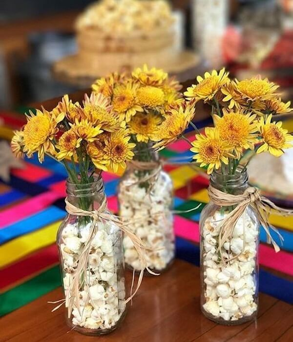 Transparent glass bottles and popcorn decorate the table of the sunflower theme party guests
