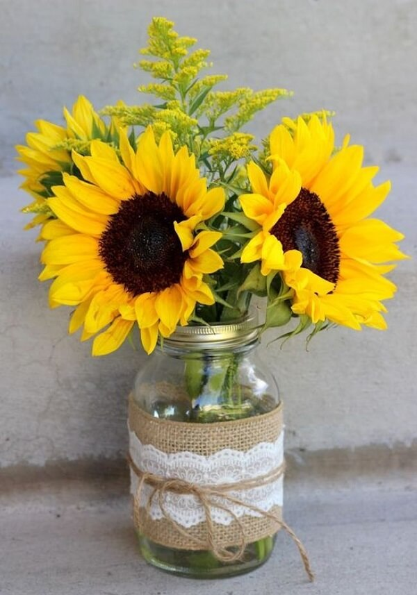 Simple decoration made with glass jar, jute fabric and sisal rope for sunflower theme party