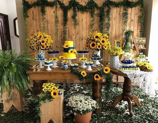 Rustic decoration for sunflower theme party with floral arrangements and wooden panel