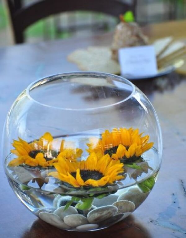 Use the transparent vase with stones, water and sunflower flowers to decorate the table