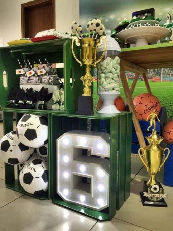 Use wooden crates, decorative letters, balls and trophy to decorate your cake table