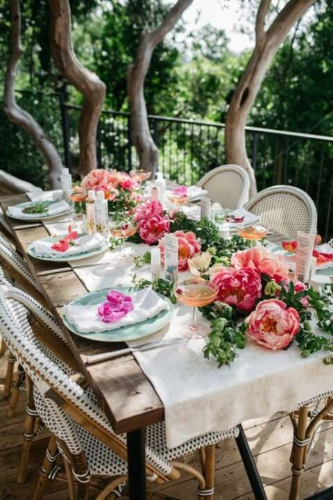 Enchanted outdoor garden party with table full of flowers Photo by Wear4Trend