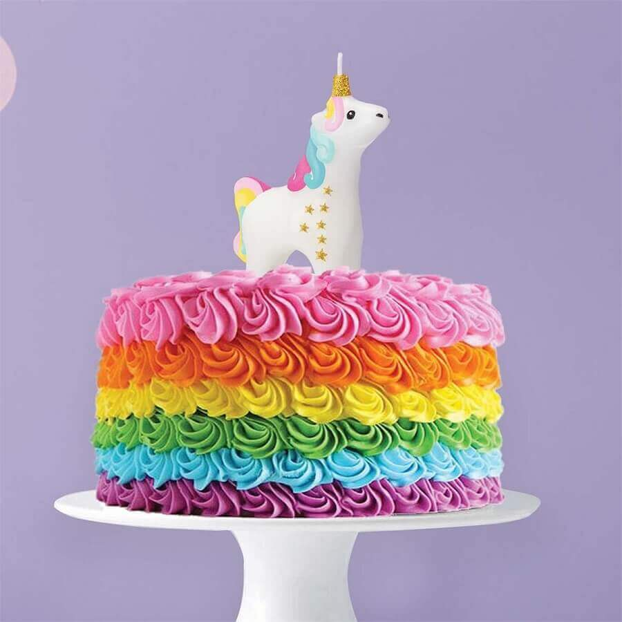 cakes decorated with colored whipped cream and unicorn candle Photo The Unicorn Store