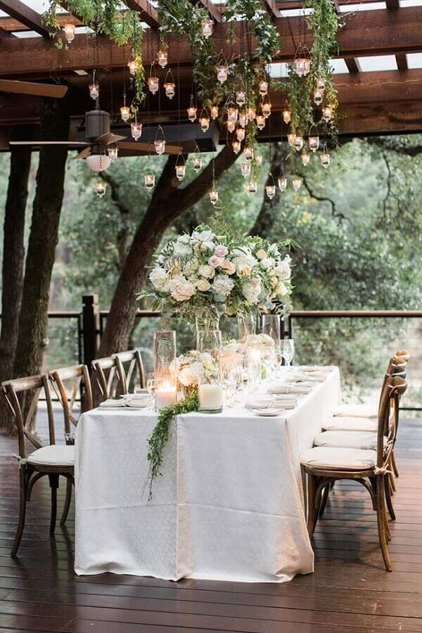 outdoor wedding party decorated with small hanging candles and rose arrangements Photo MODwedding