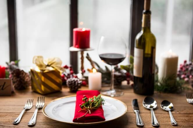 Christmas table with red napkin, wine glass and candles
