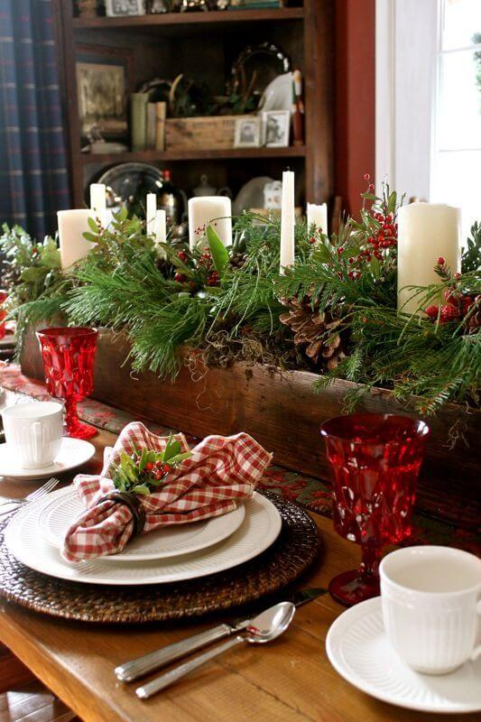 Christmas table centre with plants and candles and red bowls
