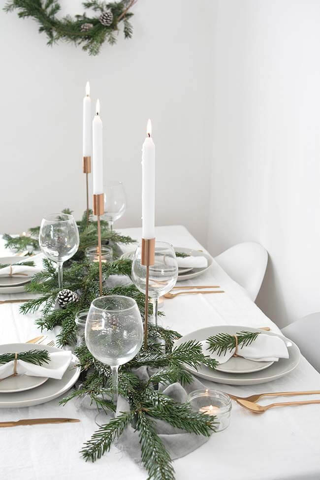 Simple Christmas table decoration with plants and tall candles
