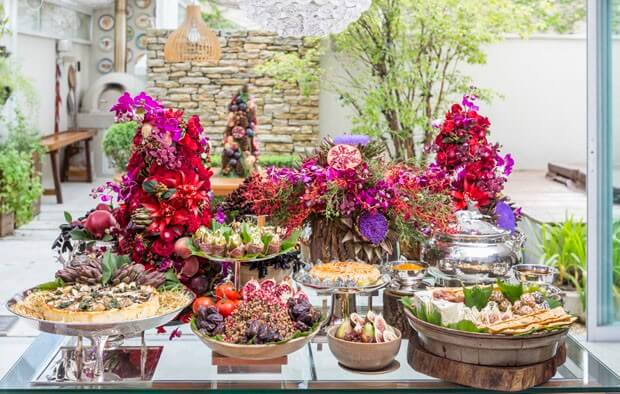 Christmas table decorated with fruit and flowers and red