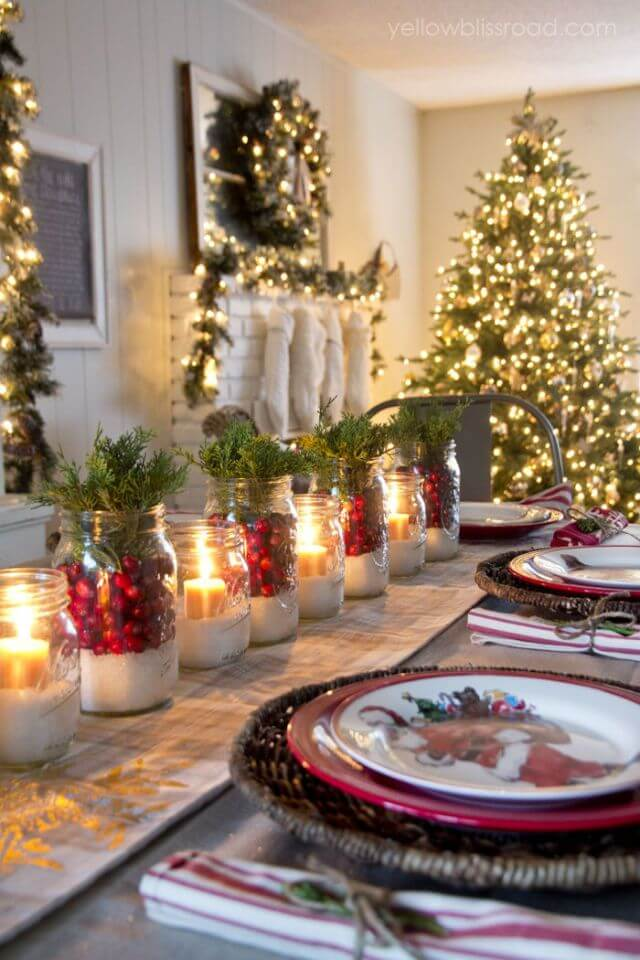 Christmas table decorated with candles and red fruits