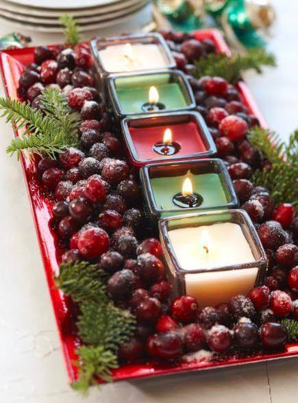 Christmas table arrangements with candles and colored fruits