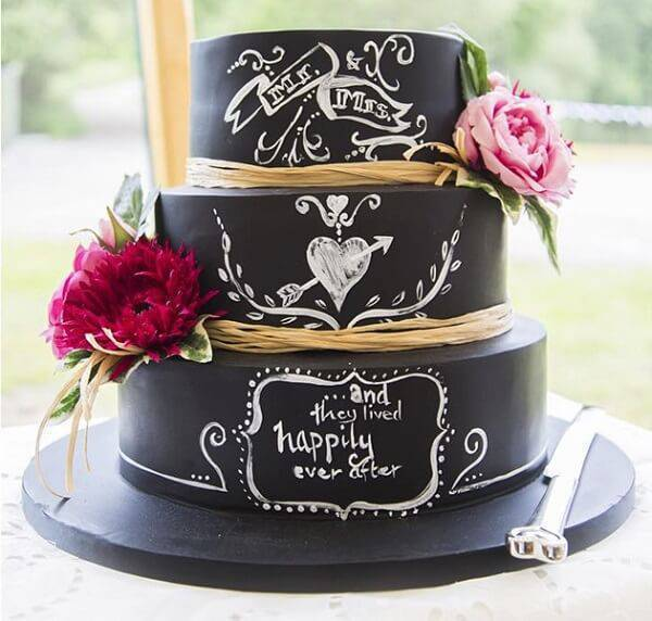 Wedding fake cake with black background, phrases and flowers on the sides