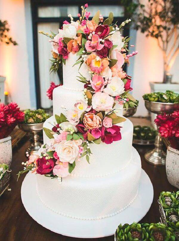 Fake wedding cake with white background and cascade of natural flowers