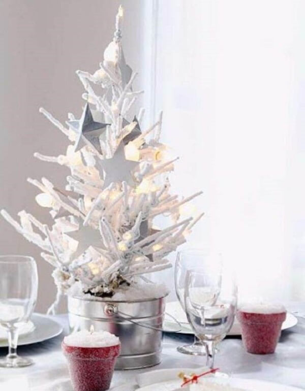 White mini Christmas tree decorates the center of the dining table
