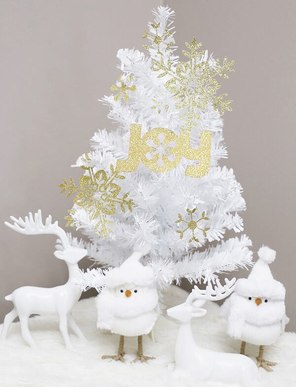 Details in gold stand out in this white Christmas tree