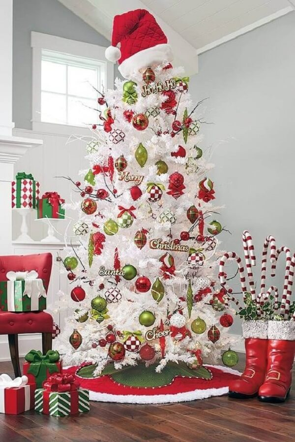 White Christmas tree full of Christmas decorations in shades of red and green
