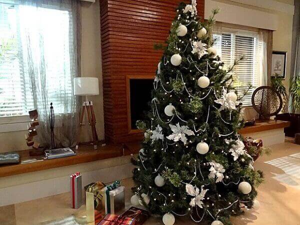 Christmas tree with white ornaments in room