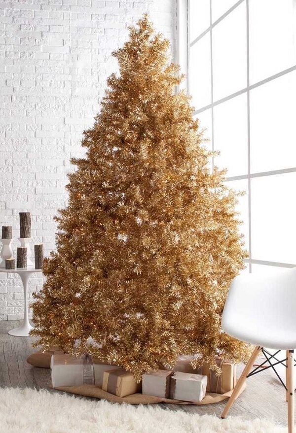 The clean white room has won a majestic golden Christmas tree