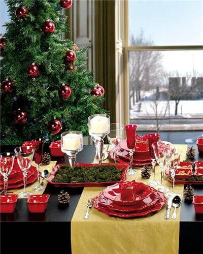 Christmas dinner table with red plates Photo by Frend