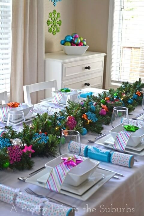 Christmas dinner table with pine branches and colorful Christmas decorations Foto deA Pretty Life in the Suburbs