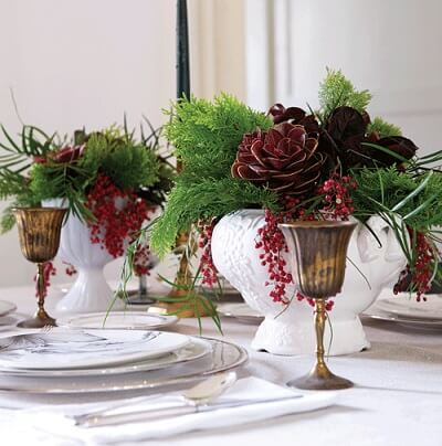 White vases with fake plants on Christmas dinner table Photo by Chatelaine
