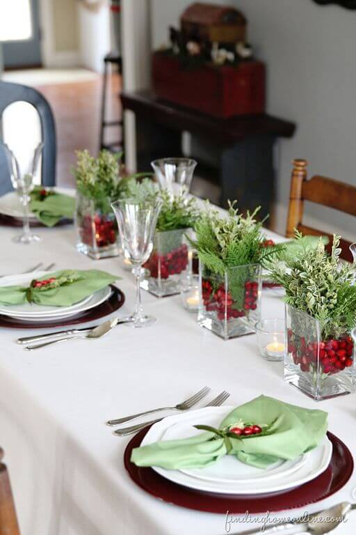 Glass Cachepot with little green and red plants on the Christmas dinner table Photo by Finding Home Online