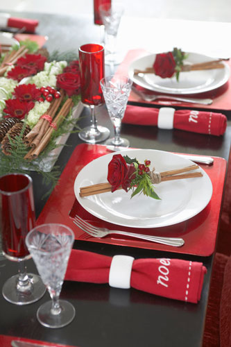Red sousplats with white dishes at Christmas dinner table Photo by Garbo