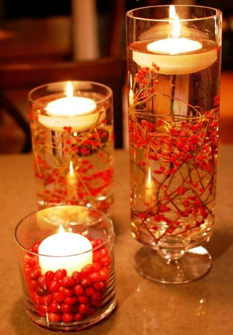 Table decorations with glasses with candles and red plants Photo by HomeBNC