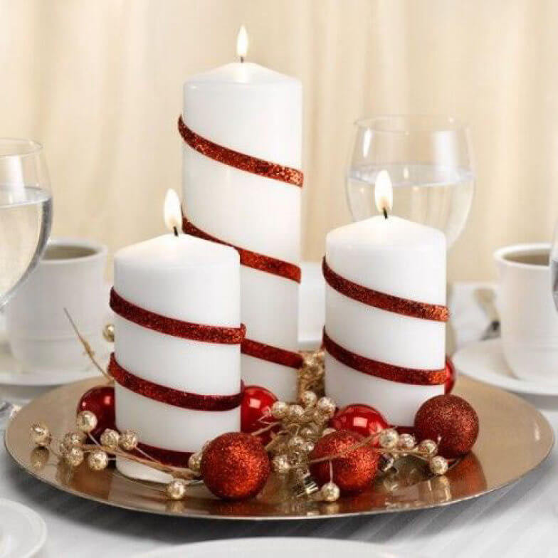 White candles with red details on Christmas dinner table Photo by HomeBNC