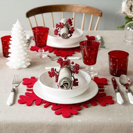 Christmas dinner table with red plate rests in snowflake format Photo by Inspira Hogar
