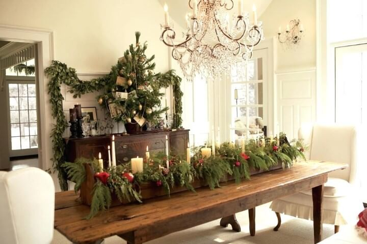 Wooden table center with candle leaves at Christmas dinner table Photo by Just Cope