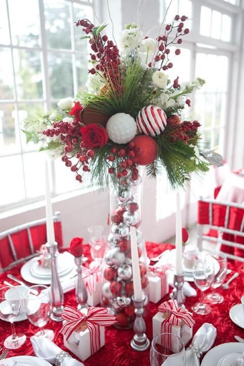 Glass pot with Christmas balls and plants on Christmas dinner table Photo by Pinterest