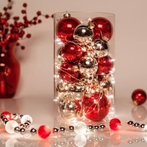 Transparent pot with Christmas balls and flashes on Christmas dinner table Photo by Pinterest
