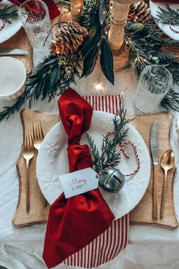 Christmas table decorated with pinecones and gold cutlery Photo Home With Holliday