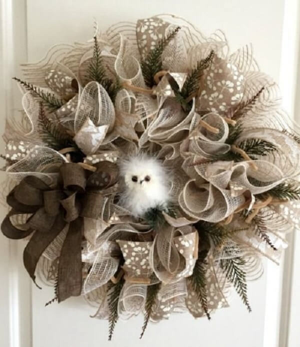 Christmas wreath with artificial flowers and details in neutral tone
