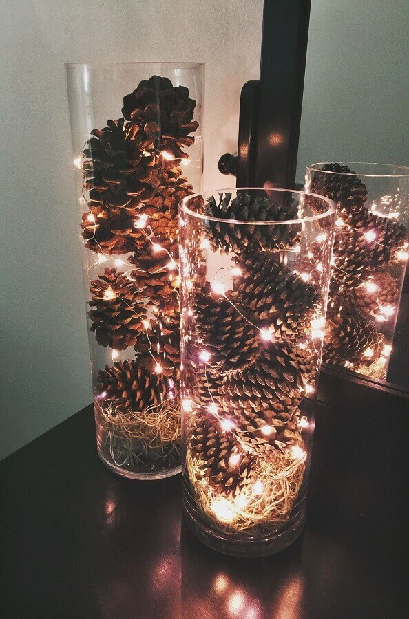Christmas arrangement with pinecones and flashing lights in glass vases Photo Pinterest