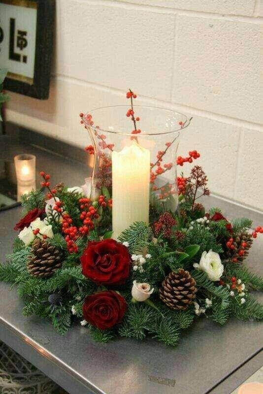 Christmas arrangement with pinecones candle and red flowers Photo MdeMulher